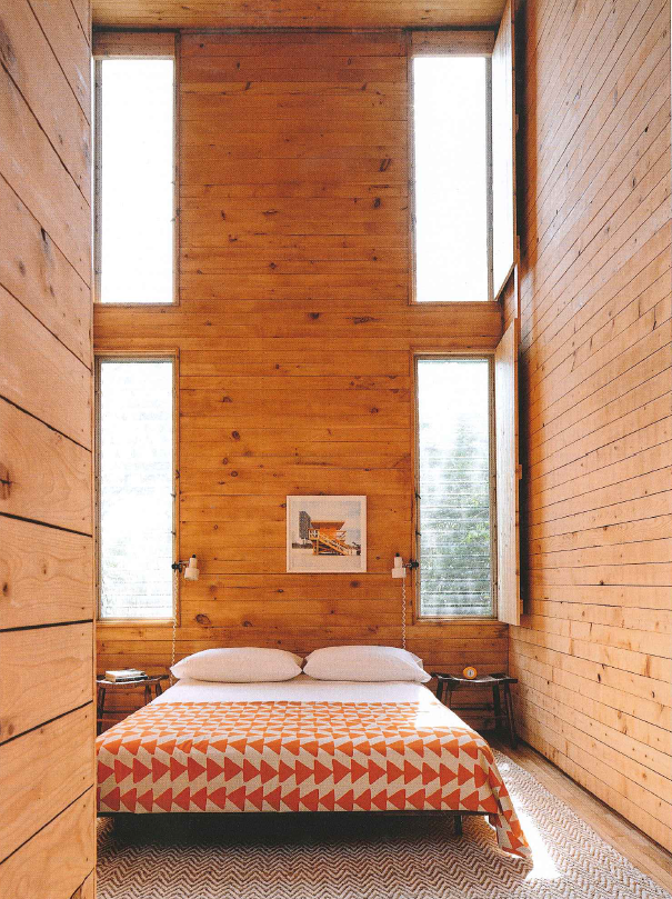 Graphic bedspread, and textured rug, add interest in this bedroom.