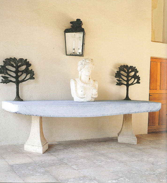 Denim covers a table on the porch, which is decorated with birds by Alberto Giacometti.
