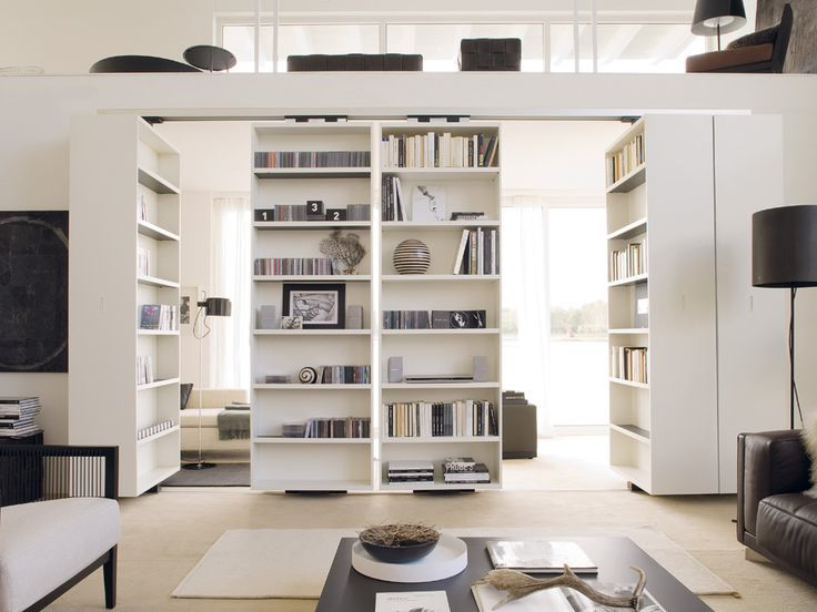 Integrate book cases into the architecture. Pivoting shelves can transform a room from living room to study, from open to closed. With the right set up, you could incorporate a television, to transform a living room into a family room with one twirl. Cool idea.