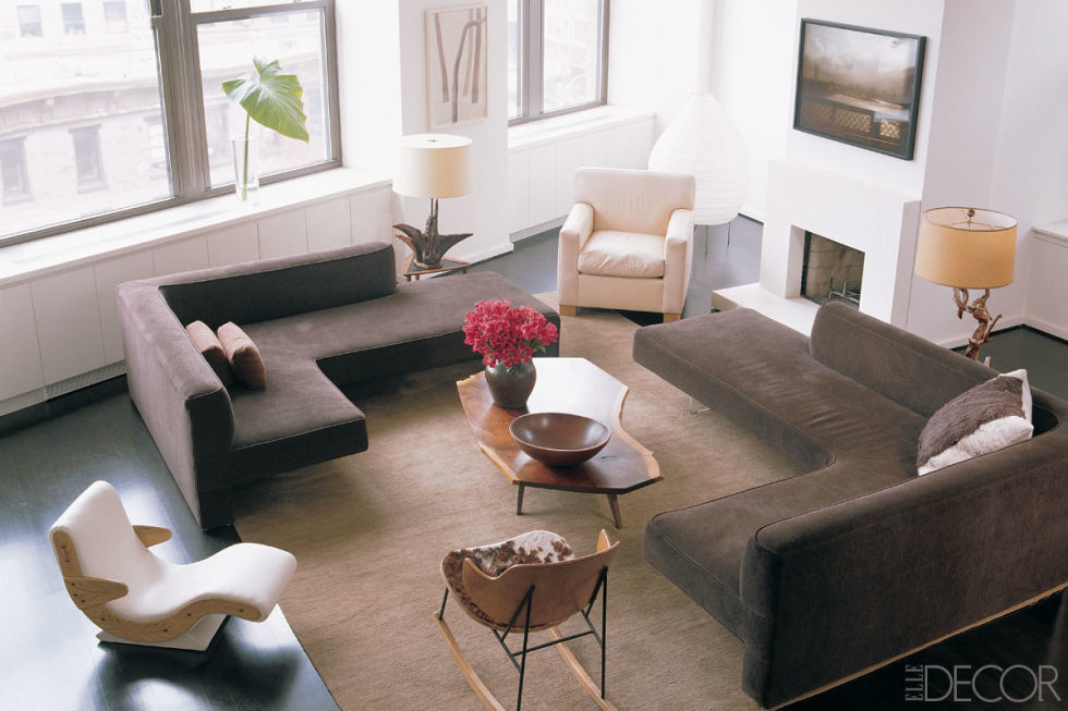Sectional sofa by Vladimir Kagan, Nakashima coffee table, and photography by Nan Goldin make this a stunning living room in Julian Moore's Tribeca home. Also notice the refined fireplace surround, and the Naguchi floor lamp.