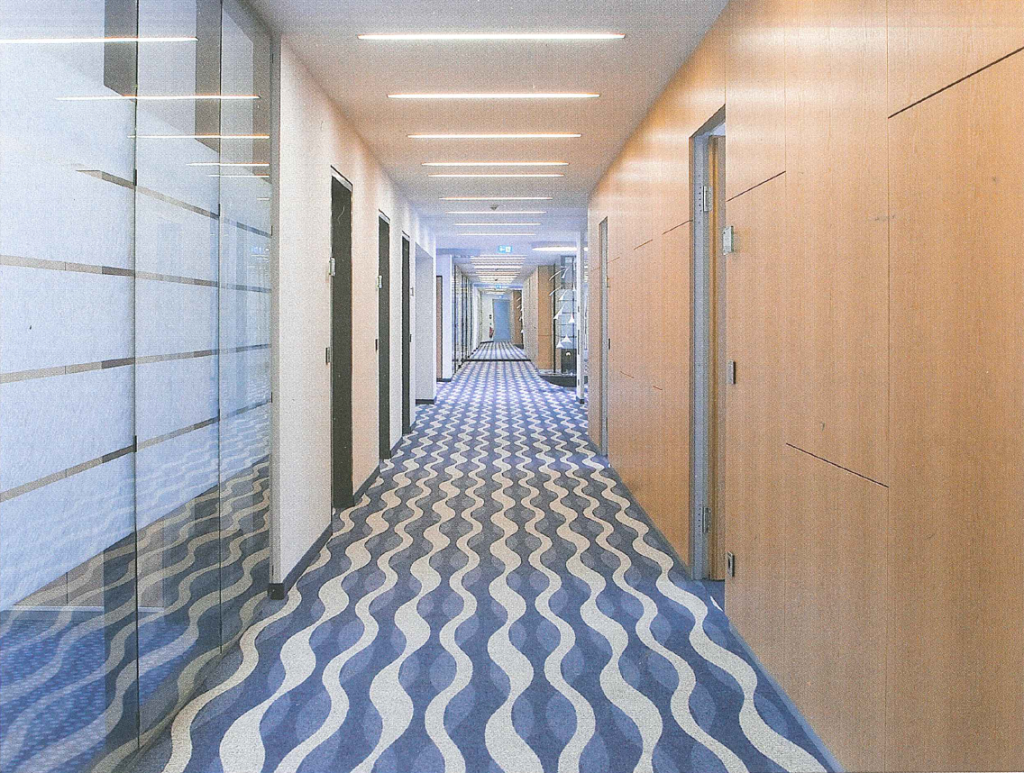 Wavy design is reflected in the glass and mirror in the hallway of Hallertauer Voksbank, Germany.