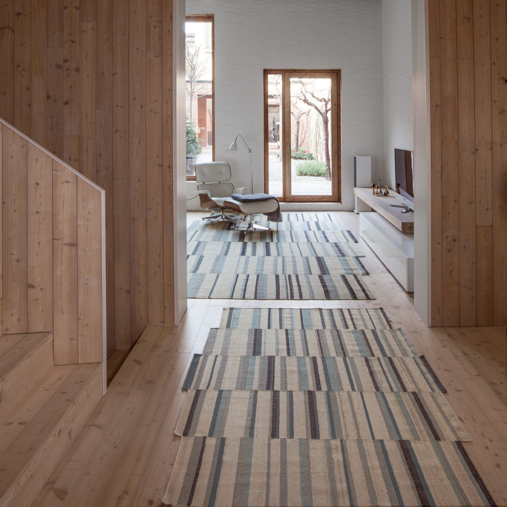 Lattice inspired rugs work great in this wood lined house. This would fit in so well here with the Bay Area design tradition.