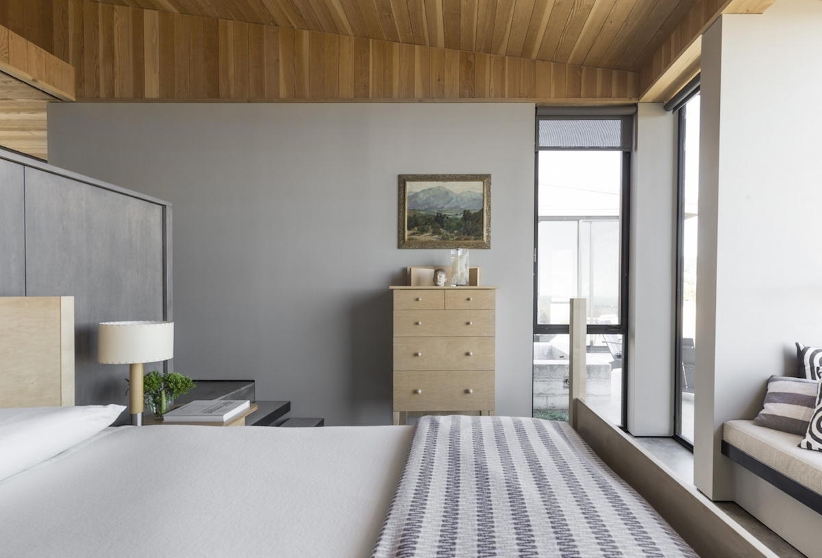 A half-height closet backs the bedroom, where window seats replace chairs. #erichburkhart #searanch #bjorndesign_ca