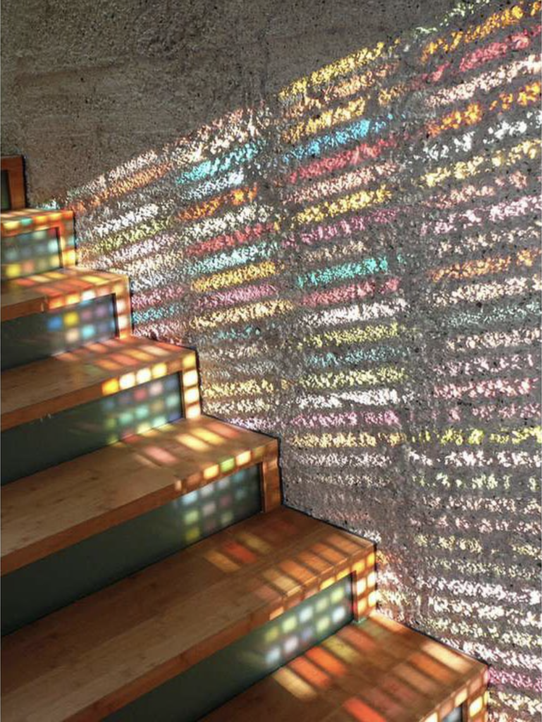 The tactility of the walls is emphasized and animated in this staircase with colored glass