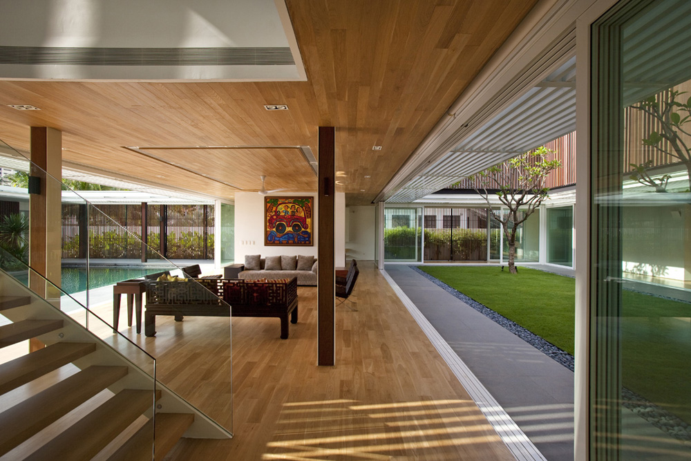 Sliding window walls open this living area onto pool and garden in Enclosed Open House by Wallflower Architecture + Design
